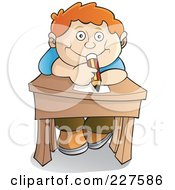 Happy Red Haired School Boy Leaning Over His Desk And Holding A Pencil