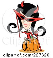 Retro Woman In A Devil Costume Sitting On A Halloween Pumpkin