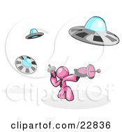 Clipart Illustration Of A Pink Man Fighting Off UFOs With Weapons by Leo Blanchette