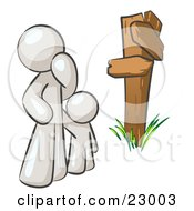 Uncertain White Man And Child Standing At A Wooden Post Trying To Decide Which Direction To Go At A Crossroads