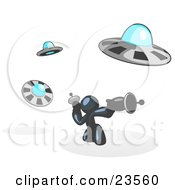 Clipart Illustration Of A Navy Blue Man Fighting Off UFOs With Weapons by Leo Blanchette
