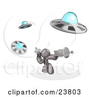 Clipart Illustration Of A Gray Man Fighting Off UFOs With Weapons by Leo Blanchette