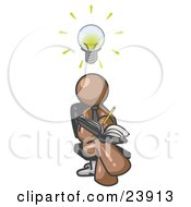 Smart Brown Man Seated With His Legs Crossed Brainstorming And Writing Ideas Down In A Notebook Lightbulb Over His Head