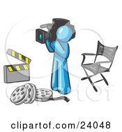 Clipart Illustration Of A Light Blue Man Filming A Movie Scene With A Video Camera In A Studio