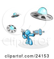 Clipart Illustration Of A Light Blue Man Fighting Off UFOs With Weapons by Leo Blanchette