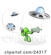 Clipart Illustration Of A Lime Green Man Fighting Off UFOs With Weapons by Leo Blanchette