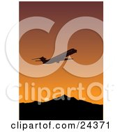 Silhouetted Commercial Airliner Flying Away During Departure Against An Orange Sunset Sky With Mountains