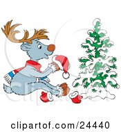 Cute Gray Reindeer With Brown Antlers Wearing A Scarf And Holding A Santa Hat While Sitting In Front Of A Snow Flocked Tree by Alex Bannykh
