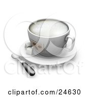 Frothy Cup With Coffee Bean Designs On Top Of A White Saucer With Two Sugar Cubes And A Spoon