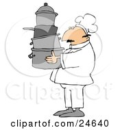 Male Chef In A White Hat And Uniform Carrying A Large Stack Of Pots Through A Kitchen