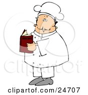 White Male Chef In A White Uniform And Hat Standing And Reading A Recipe Book In A Kitchen