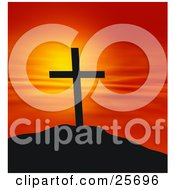 Cross On Top Of A Hill Silhouetted Against A Red And Orange Sunset