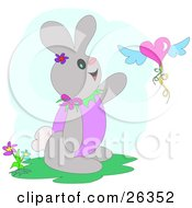 Clipart Illustration Of A Happy Bunny Rabbit By Flowers Trying To Grasp A Heart Shaped Balloon With Wings