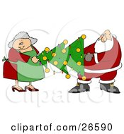 Mrs Claus Helping Santa Carry A Decorated Xmas Tree With Lights And Baubles