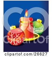 Red Candle On A Tray Casting Light On Red And Green Christmas Ornaments With Snowflake Designs Over Blue