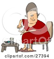 Diabetic White Woman In A Red Nightgown Sitting In A Chair At A Table And Pricking Her Finger With A Lancing Device For A Blood Sample