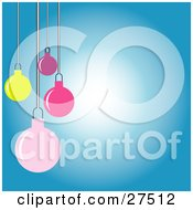Yellow Pink And Purple Christmas Tree Ornaments Hanging Over A Gradient White To Blue Background by KJ Pargeter