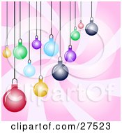 Group Of Yellow Green Blue Red And Pink Christmas Ornaments Suspended Over A Swirling Pink Background