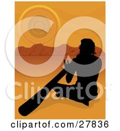 Silhouetted Aboriginal Man Sitting In The Sand And Playing The Didgeridoo In The Australian Outback