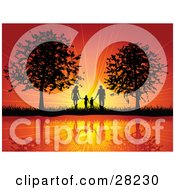 Clipart Illustration Of A Silhouetted Family Of Four Holding Hands And Walking Between Two Trees Reflecting On Still Water Against A Bursting Orange Sunset