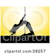 Flexible Black Silhouetted Pole Dancer Woman Holding Onto The Pole And Leaning Backwards While Dancing On Stage Over A Yellow Background