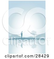 Clipart Illustration Of A Lone Silhouetted Man Standing Near Hills And A Tree Reflecting On The Still Waters Of A Lake On A Foggy Morning