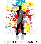 Clipart Illustration Of A Black Mostly Silhouetted Man Standing With His Arms Crossed On A Reflective White Surface With A Background Of Blue Yellow And Red Paint Splatters by KJ Pargeter