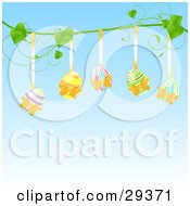 Five Colorful Easter Eggs Hanging From Golden Ribbons On A Green Vine Over A Blue Background