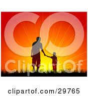 Silhouetted Girl Holding Hands With A Man Father And Daughter Walking In Grass Towards An Orange Sunset