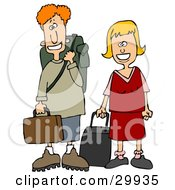 Young White Couple Smiling And Standing With Their Luggage At An Airport