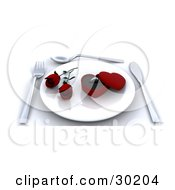 Place Setting Of A Ring In A Heart Box With Two Red Roses On A Plate With A Fork Knife And Spoon On A Table
