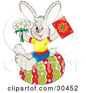 Clipart Illustration Of A Dressed Bunny Rabbit Holding Spring Daisy Flowers And A Greeting Card While Sitting On A Colorful Easter Egg