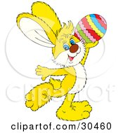 Yellow Easter Bunny Prancing And Holding Up A Colorful Easter Egg by Alex Bannykh
