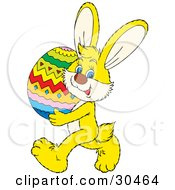 Clipart Illustration Of A Cute Yellow Rabbit Carrying A Large Colorful Easter Egg