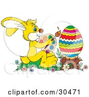 Clipart Illustration Of A Cute Yellow Bunny Rabbit Sitting In Flowers Holding A Palette And Paint Brush And Painting A Large Easter Egg Propped On A Stump by Alex Bannykh