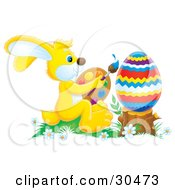 Clipart Illustration Of An Artistic Yellow Easter Bunny Holding A Palette And Paintbrush And Painting A Large Easter Egg Resting On A Stump