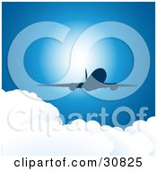 Silhouetted Commercial Airplane Flying Above Puffy White Clouds In A Blue Sky With Sunlight