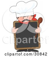Male Chef With A Mustache Wearing A Hat And Holding A Wood Spoon While Pointing To A Blank White Chalkboard