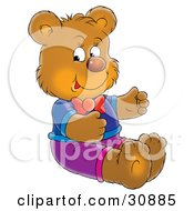 Bear Cub Wearing Clothing Sitting On The Floor And Smiling
