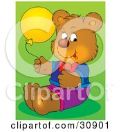 Happy Brown Birthday Bear Dressed In Clothes Holding A Yellow Party Balloon Over A Green Background