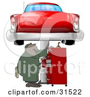 Black Male Mechanic Looking For Tools In A Red Tool Box Under A Red Classic Car Up On A Lift In A Garage