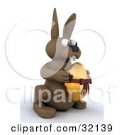 Clipart Illustration Of A Brown 3d Bunny Holding A Golden Easter Egg With A Bow On It