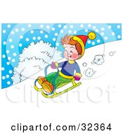 Boy Riding Downhill On A Sled On A Snowy Winter Day