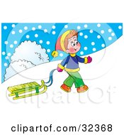 Happy Little Boy Pulling His Sled Up A Hill On A Snowy Winter Day