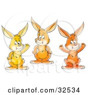 Clipart Illustration Of A Group Of Three Friendly Orange And Yellow Bunny Rabbits