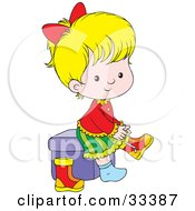 Little Blond Girl Sitting On A Cube And Putting Her Boots On