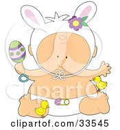 Baby In Bunny Ears And Diaper Holding A Rattle And Playing With Chicks