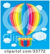 Clipart Illustration Of A Colorful Red Orange Yellow Green Blue And Pink Striped Hot Air Balloon In A Blue Cloudy Sky by Alex Bannykh