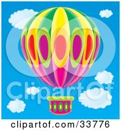 Clipart Illustration Of A Colorful Oval Patterned Hot Air Balloon In A Blue Cloudy Sky by Alex Bannykh