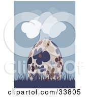 Beige Easter Egg With Colorful Flower Patterns Resting In Blue Grass Under A Cloudy Blue Sky